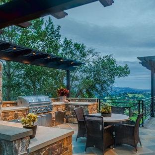 Diseño de patio tradicional renovado, extra grande, en patio lateral, con cocina exterior, adoquines de piedra natural y pérgola