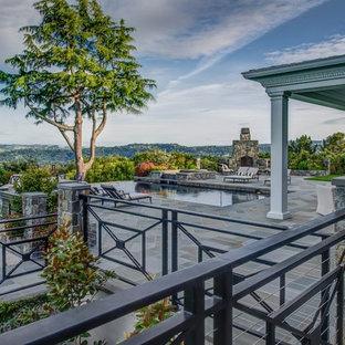 Foto di un ampio patio o portico chic dietro casa con un focolare, pavimentazioni in pietra naturale e un gazebo o capanno