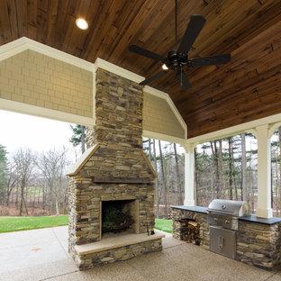 Immagine di un grande patio o portico stile americano dietro casa con un focolare, graniglia di granito e un tetto a sbalzo