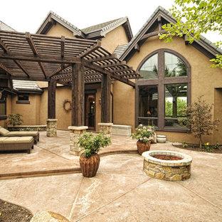 Esempio di un grande patio o portico stile americano dietro casa con un focolare, cemento stampato e una pergola