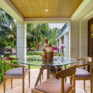 Foto di un piccolo patio o portico tropicale dietro casa con piastrelle e un tetto a sbalzo