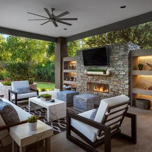 Idee per un grande patio o portico design dietro casa con piastrelle, un tetto a sbalzo e un caminetto