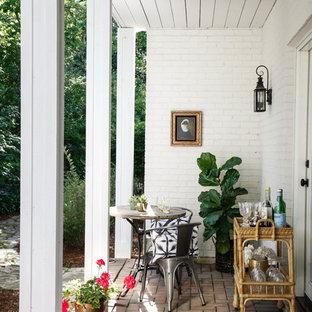 Foto di un patio o portico classico con un giardino in vaso, pavimentazioni in mattoni e un tetto a sbalzo