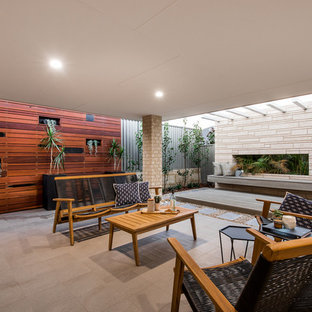 Design ideas for a mid-sized contemporary backyard patio in Perth with tile and a roof extension.