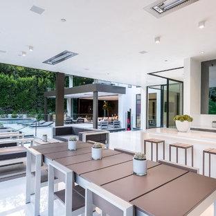 Idee per un ampio patio o portico moderno dietro casa con un tetto a sbalzo e piastrelle