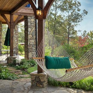 Esempio di un patio o portico stile rurale con pavimentazioni in pietra naturale e un tetto a sbalzo
