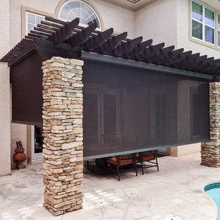 Example of a mid-sized classic backyard stone patio design in Austin with an awning