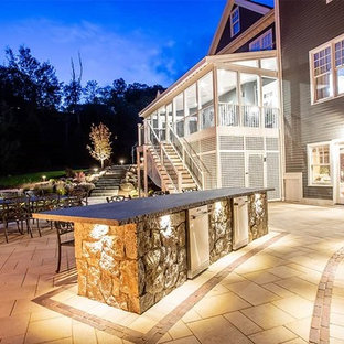 Modern back patio in Bridgeport with an outdoor kitchen, natural stone paving and an awning.