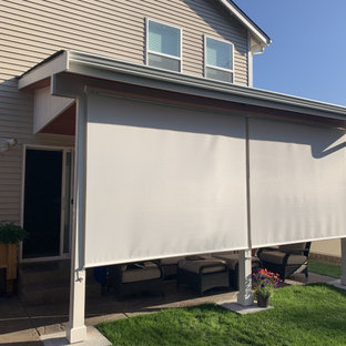 Photo of a medium sized rural back patio in Seattle with an outdoor kitchen, concrete slabs and an awning.