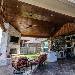 Cette image montre une terrasse arrière traditionnelle avec du béton estampé et une extension de toiture.