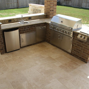 Large elegant backyard stone patio kitchen photo in Houston with a roof extension