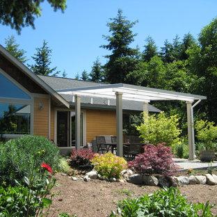 Ispirazione per un patio o portico country di medie dimensioni e dietro casa con lastre di cemento e un parasole