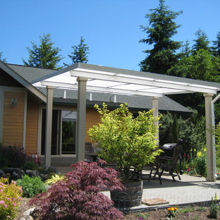 Photo of a medium sized rural back patio in Seattle with concrete slabs and an awning.