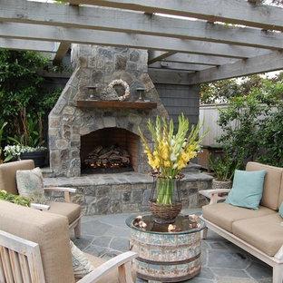 Idee per un patio o portico stile marinaro con un focolare e una pergola