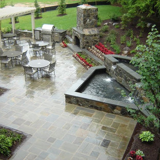 Example of a classic patio design in Baltimore with a fire pit and a gazebo