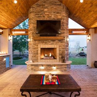 Ispirazione per un patio o portico stile rurale dietro casa con cemento stampato e un tetto a sbalzo