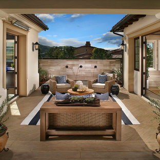 Expansive mediterranean courtyard patio in San Diego with a water feature, tile and a roof extension.