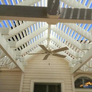 Große Rustikale Pergola hinter dem Haus mit Outdoor-Küche und Natursteinplatten in Sonstige