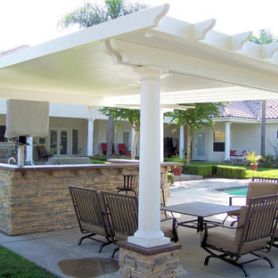 Design ideas for a medium sized mediterranean back patio in Other with an outdoor kitchen, concrete slabs and a pergola.