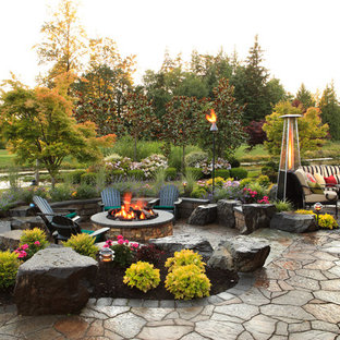 Example of a classic stone patio design in Seattle with a fire pit and no cover
