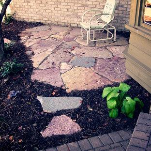 Foto di un piccolo patio o portico classico nel cortile laterale con pavimentazioni in pietra naturale e un tetto a sbalzo