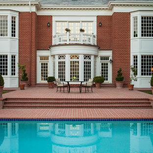 Immagine di un ampio patio o portico classico dietro casa con pavimentazioni in mattoni