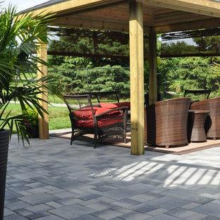 Imagen de patio grande, en patio trasero, con jardín de macetas, adoquines de piedra natural y pérgola