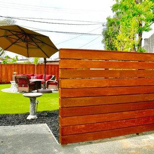 Ispirazione per un patio o portico design di medie dimensioni e nel cortile laterale con un focolare, pavimentazioni in cemento e un parasole