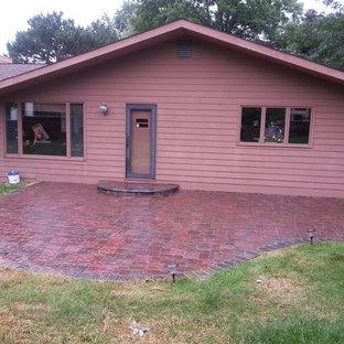 Esempio di un patio o portico minimalista di medie dimensioni e nel cortile laterale con pavimentazioni in mattoni