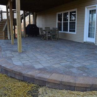 Idee per un piccolo patio o portico stile americano dietro casa con pavimentazioni in cemento e un tetto a sbalzo