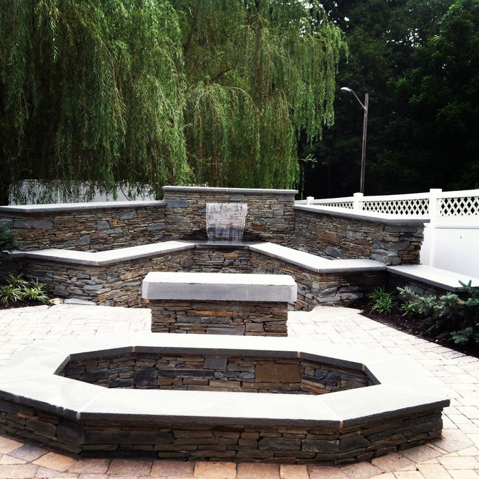 paver patio with waterwall , bluestone walls and unique bluestone firepit