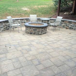 Idee per un patio o portico stile rurale di medie dimensioni e dietro casa con pavimentazioni in cemento, nessuna copertura e un focolare