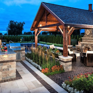Design ideas for a medium sized classic back patio in Chicago with brick paving, an outdoor kitchen and a gazebo.
