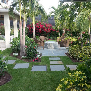 Inspiration for a tropical stone patio remodel in Miami with a fire pit