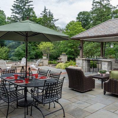 Patio kitchen - mid-sized traditional backyard stone patio kitchen idea with a gazebo