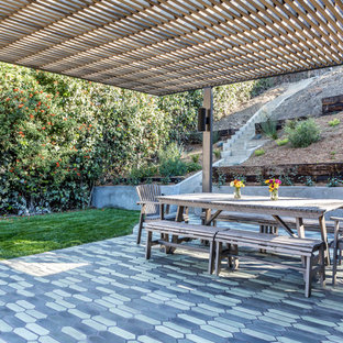 Medium sized farmhouse back patio in Los Angeles with tiled flooring and an awning.