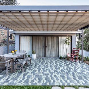 Esempio di un patio o portico country di medie dimensioni e dietro casa con piastrelle e una pergola