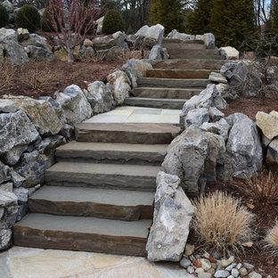 Idee per un grande patio o portico american style dietro casa con un focolare, pavimentazioni in pietra naturale e nessuna copertura