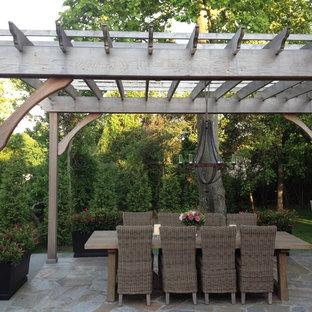 Idee per un patio o portico country dietro casa con pavimentazioni in pietra naturale e una pergola