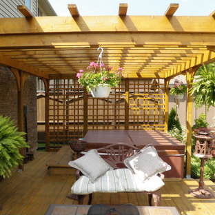 Example of a mid-sized classic backyard patio design in Toronto with decking and a pergola