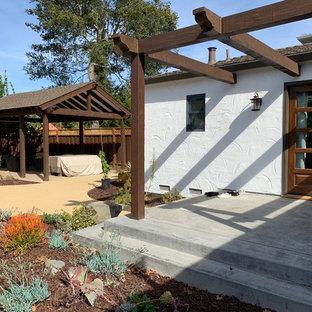 Esempio di un patio o portico stile shabby di medie dimensioni e dietro casa con cemento stampato e una pergola