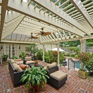 Idee per un grande patio o portico tradizionale dietro casa con una pergola, fontane e pavimentazioni in mattoni
