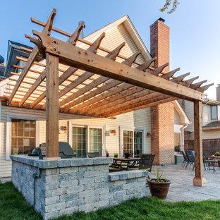 На фото: пергола во дворе частного дома на заднем дворе в классическом стиле с летней кухней с