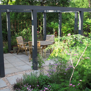 Medium sized contemporary back patio in London with natural stone paving and a pergola.