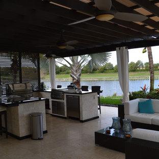 Ispirazione per un ampio patio o portico tropicale dietro casa con pavimentazioni in pietra naturale e una pergola