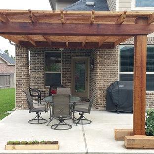Ispirazione per un patio o portico american style di medie dimensioni e dietro casa con lastre di cemento e una pergola