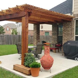 Immagine di un piccolo patio o portico american style dietro casa con lastre di cemento e una pergola