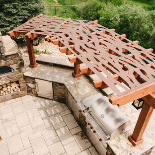 Example of a large arts and crafts backyard tile patio kitchen design in Dallas with a pergola