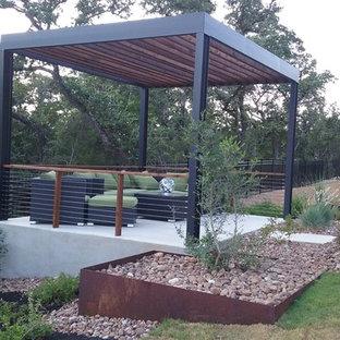 Ejemplo de patio de tamaño medio, en patio trasero, con adoquines de hormigón y pérgola
