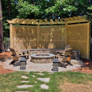 Esempio di un patio o portico classico di medie dimensioni e dietro casa con pavimentazioni in pietra naturale, una pergola e un focolare